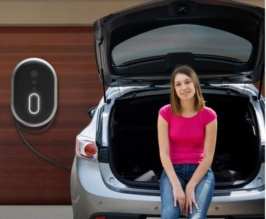 Chica en vehículo eléctrico cargando las baterías en su casa con su punto de carga